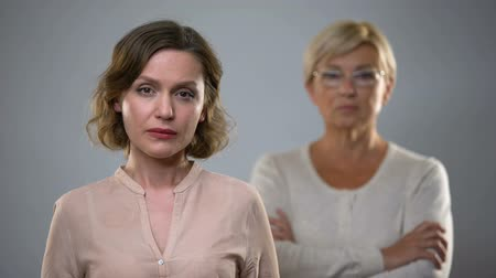 scandal : Sad young woman looking in camera, strict senior mother standing behind, problem