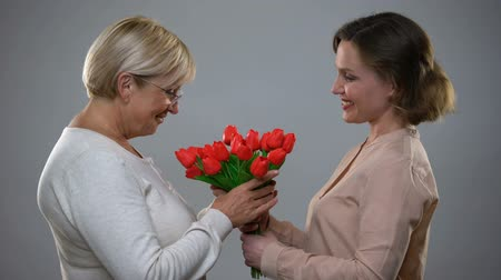 bouquets : Caring daughter giving red tulips to mature mother, international women day