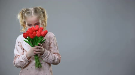 cheirando : Adorable girl smelling flowers and smiling on grey background, holiday mood Stock Footage