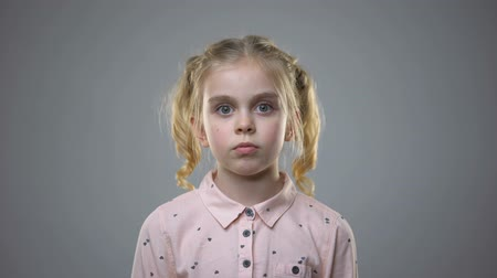 испуг : Scared female kid standing grey background, frightened child, orphanage bullying