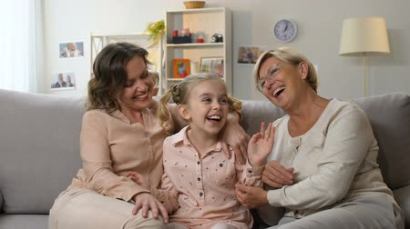 trusting : Little school girl laughing with mother and granny, family having fun together