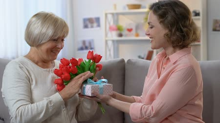 şükran : Caring daughter giving flowers and gift box to mother on 8 March, family love
