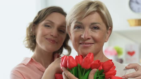osm : Portrait of adult daughter and mother holding tulips, celebrating Women Day