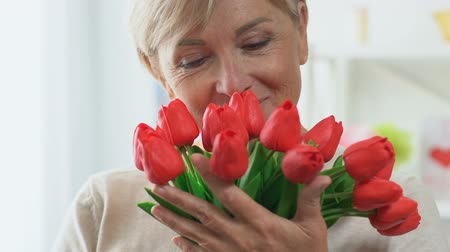 感謝の気持ち : Middle-aged mother smelling tulips, smiling happily, wrinkles on face closeup