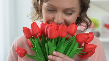 eight : Beautiful woman smelling tulips, smiling into camera, celebrating 8 March