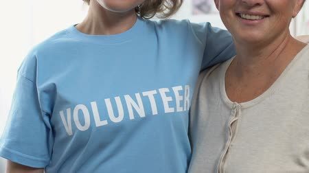 solidarność : Two women pointing at Volunteer word on t-shirt, offer jobs to help people Wideo