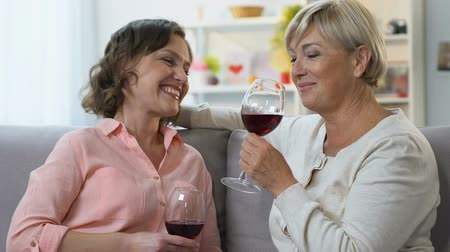 trusting : Two women drinking wine, having casual conversation, sharing positive news