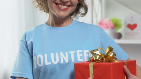 altruism : Volunteer holding presents for orphaned children, charity holidays, sponsorship Stock Footage