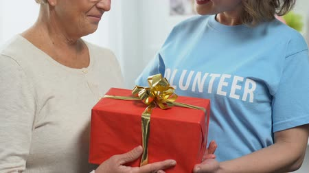 philanthropy : Volunteer giving birthday gift to pensioner, charity concept, financial support Stock Footage