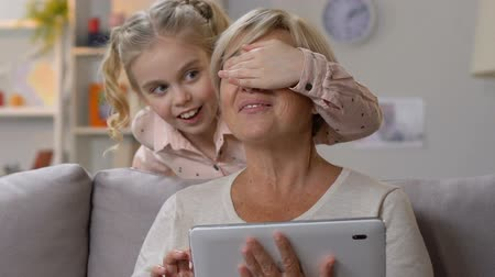 lembrete : Granny checking holidays app on tablet, celebrating birthday with granddaughter