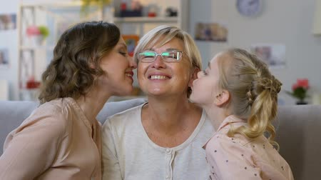 harts : Cute girl and her mom kissing granny, family embracing heartily, happy together