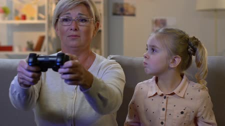 lack : Funny little girl taking joystick away from granny to play video game, addiction