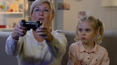 lack : Grandmother ignoring child while playing video game with console, addiction