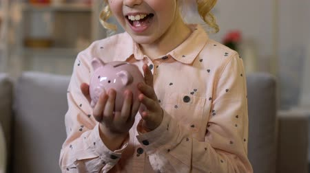 alfabetização : Little girl putting coin into piggy bank, saving money for child dream, closeup Vídeos