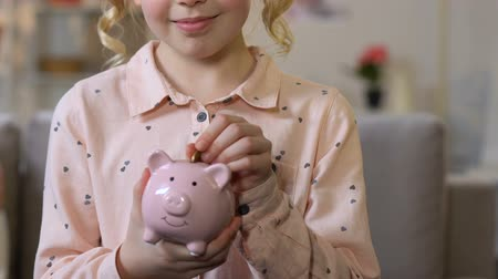 alfabetização : Adorable girl putting coin into piggy bank, funds from early childhood, closeup