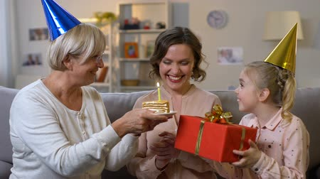 parentes : Young woman blowing birthday candle, receiving presents from loving family Stock Footage
