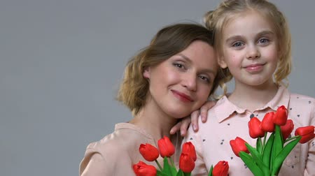 dankbaarheid : Portrait of mother and daughter holding tulips, femininity and spring mood Stockvideo