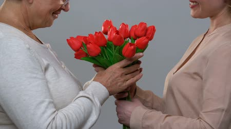 eight : Loving daughter congratulating mom happy birthday, giving flowers in gratitude Stock Footage