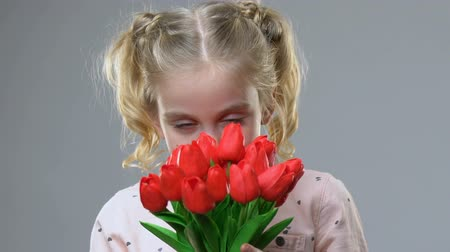 bouquets : Adorable girl smelling flowers, enjoying spring time, femininity and tenderness