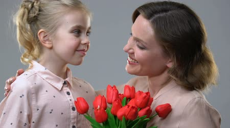 parentes : Cute girl giving flowers to beloved mother, surprise for birthday or March 8