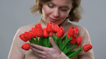 vůně : Cheerful woman enjoying scent of flowers, concept of femininity and beauty
