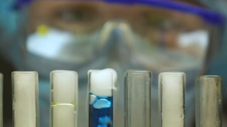 合成 : Lab expert looking at test tube with evaporating liquid, illegal laboratory