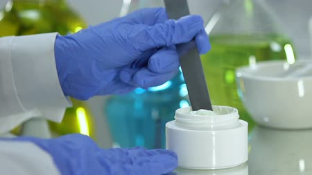 consistency : Beauty lab chemist taking creme sample, organic dermatology cosmetics production