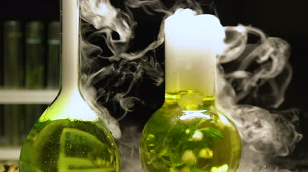 oxigênio : Chemical liquids in flasks boiling emitting smoke on dark background, extracting Stock Footage