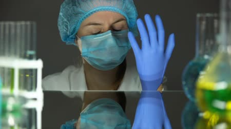 veiligheidsbril : Scientist putting on gloves at working day beginning, protective uniform