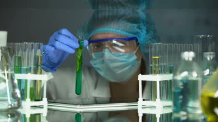 biologa : Scientist checking plant in preservative agent, adding info to tab, innovations