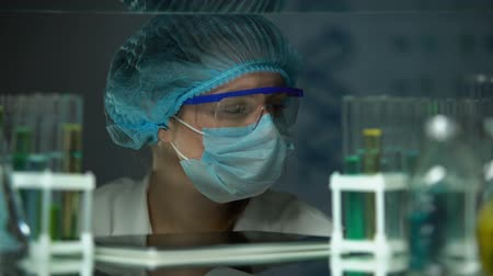chemical agent : Scientist analyzing tubes with liquids and checking results on tab, innovations Stock Footage
