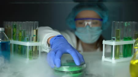 influence : Lab assistant taking green powder from fridge, dermatology cryotherapy material