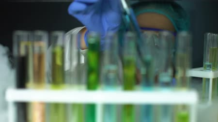 chemical agent : Lab assistant taking tube with blue test liquid from fridge, checking reaction