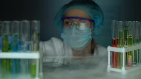 chemical agent : Chemist opening fridge, dripping liquid in tube with red transparent substance Stock Footage