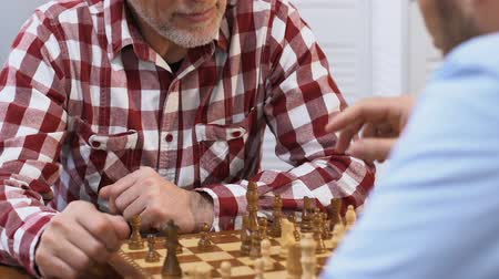 общий : Two male friends playing chess, thinking over strategy, common hobby, close-up