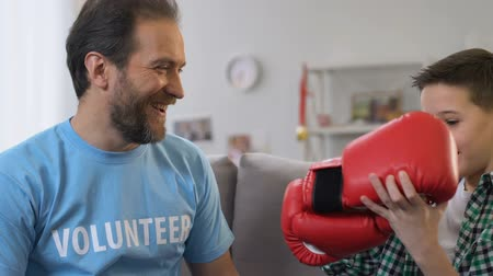 realizing : Male volunteer realizing dream of little boy orphan, presenting boxing gloves