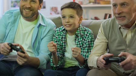 támogató : Father and grandpa playing video game at home, boy cheering for victory, relax