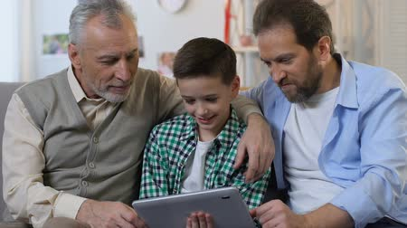 use computer : Family using tablet together at home, birthday gift for little boy, generation Stock Footage