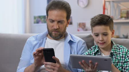lack : Boy using tablet, father scrolling on smartphone at home, lack of communication Stock Footage