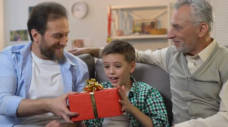 eyes closed : Boy sitting with eyes closed, father and grandpa giving birthday gift, surprise Stock Footage