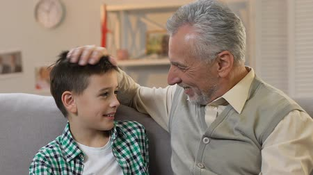 поглаживание : Grandpa stroking grandson head, hugging and looking at camera, family time