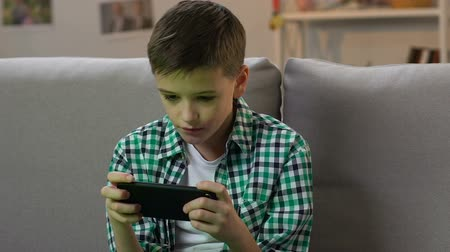 atirador : Boy playing video game on smartphone at home, gadget addiction in young age