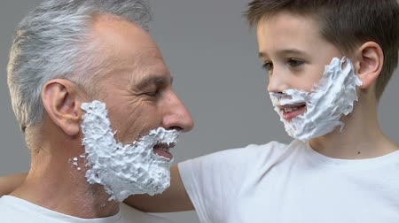 navalha : Old man and grandson with shaving foam on faces showing razors into camera