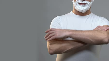 shaving foam : Confident man standing with hands crossed and shaving foam on face, hygiene Stock Footage