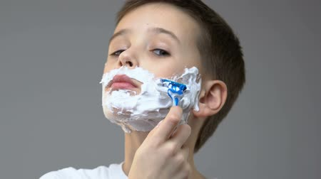 navalha : Boy with foam on face shaving in front of mirror, simulating fathers habit Stock Footage