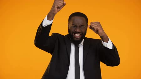 gesticulando : Happy emotional afro-american manager smiling and making yes gesture, winner