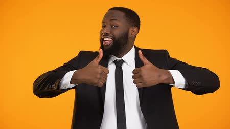 self promotion : Joyful african-american businessman showing thumbs-up, lucrative proposition