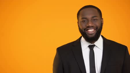 харизматический : Cheerful african-american male in formal suit smiling and looking to camera