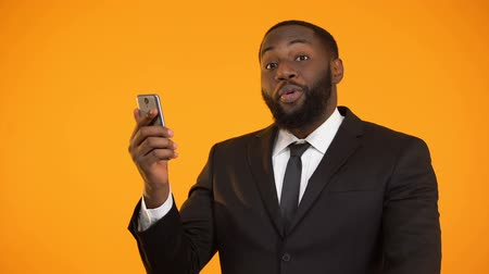 харизматический : Satisfied with mobile application performance black male showing thumbs-up