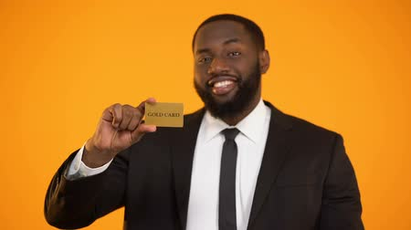 elite : Smiling confident afro-american businessman showing gold card and ok gesture